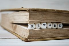 Сформулируйте вознаграждение написанное в деревянных блоках в книге стоковые фотографии rf