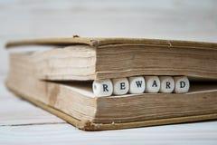 Сформулируйте вознаграждение написанное в деревянных блоках в книге стоковое изображение rf