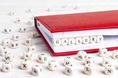 Сформулируйте галерею написанную в деревянных блоках в красной тетради на белом w стоковые фотографии rf
