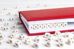 Сформулируйте приключение написанное в деревянных блоках в красной тетради на белизне стоковое фото rf