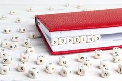 Сформулируйте финансирование написанное в деревянных блоках в красной тетради на белом w стоковая фотография