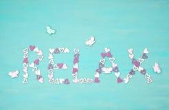 Сформулируйте RELAX сделанный малых розовых сердец над голубой предпосылкой Welln стоковые фотографии rf