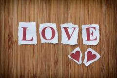 Сформулируйте влюбленность и 2 бумажных сердца на деревянной предпосылке текстуры Стоковое Фото