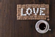 Сформулируйте влюбленность сделанную из коричневых и белых сахаров и чашки кофе Стоковое Изображение