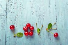 Сформулируйте влюбленность сделанную с вишнями на старой доске Стоковые Изображения RF