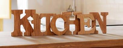 Сформулируйте кухню сделанную от деревянных писем на деревянном столе Стоковые Изображения RF