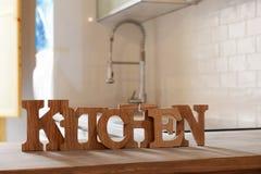 Сформулируйте кухню сделанную от деревянных писем на деревянном столе в кухне Стоковое Изображение