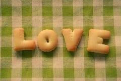 Сформулируйте печенья печений алфавита ВЛЮБЛЕННОСТИ на картине шотландки с ретро Стоковая Фотография