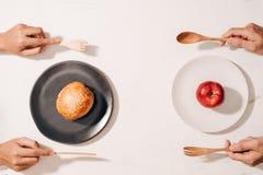 Схватка диеты и решать между дилеммой питания отборной между здоровыми хорошими свежими фруктом и овощем или богачами холестерола стоковые фотографии rf