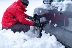Схватывать цепи снега Цепи снега на колесах автомобиля человек пробует положить цепи снега на автошины стоковое фото