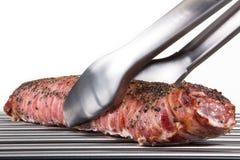 Схваты барбекю хватают большую часть свинины жаркого, изолированную на wh Стоковое Изображение