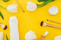 Схематическая предпосылка бутылки шампуня, дух, сливк и белых тюльпанов цветет на желтой предпосылке Состав красоты плоское Ла Стоковые Фотографии RF