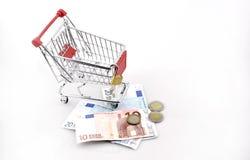 Схематическая студия сняла пука банкнот евро заполняя магазинную тележкау на белой предпосылке 18-ое сентября 2016 Стоковые Изображения