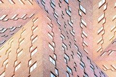 Схематическая текстура архитектуры современных кирпичных зданий с много придает квадратную форму окнам Стоковая Фотография RF