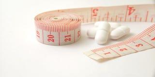 Схематический макрос, пластиковый розовый метр портноя и белые таблетки, иллюстрация для лекарства контролируя для держат здоровы стоковые фотографии rf