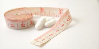 Схематический макрос, пластиковый розовый метр портноя и белые таблетки, иллюстрация для лекарства контролируя для держат здоровы стоковое изображение