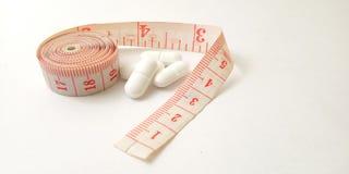 Схематический макрос, пластиковый розовый метр портноя и белые таблетки, иллюстрация для лекарства контролируя для держат здоровы стоковое изображение rf