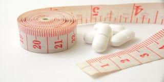 Схематический макрос, пластиковый розовый метр портноя и белые таблетки, иллюстрация для лекарства контролируя для держат здоровы стоковая фотография rf