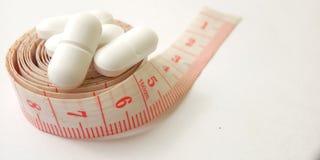 Схематический макрос, пластиковый розовый метр портноя и белые таблетки, иллюстрация для лекарства контролируя для держат здоровы стоковые фото