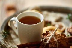 Схематический праздничный состав с чашкой горячих чая, печений и spicies на деревянном бочонке, малой глубины поля Стоковые Изображения RF