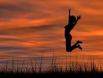 Схематический скакать силуэта молодой женщины счастливый на траве на заходе солнца стоковое фото rf