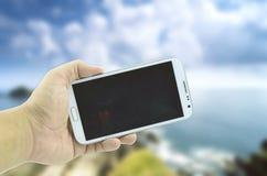 Схематическим рука подрезанная изображением держа мобильный телефон Стоковые Фото