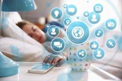 Схематическое изображение женщины в кровати используя социальные средства массовой информации на телефоне Стоковая Фотография