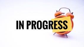 Схематическое изображение концепции дела с словами в прогрессе на часах с белой предпосылкой Селективный фокус Стоковая Фотография RF