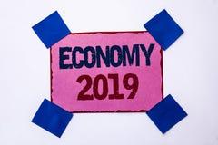 Схематическое сочинительство руки показывая экономику 2019 Заработки рынка роста валюты текста фото дела финансовые торгуют деньг Стоковые Фото