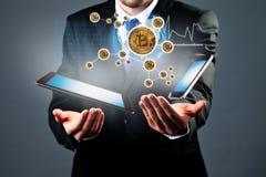 Схема цифров с рукой бизнесмена с bitcoins, таблеткой и s Стоковое Изображение