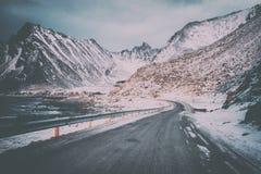 Сценарная дорога зимы через снежные скалистые горы к деревне Vikten на атлантическом береге, Lofoten, Норвегии стоковые изображения rf