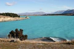 Сценарная прибрежная полоса озера с изумительной темной водой сизоватого зеленого цвета, дистантными деревьями и горами стоковое изображение rf