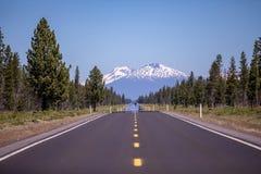 Сценарная пустая дорога асфальта водя к далекой горе стоковые изображения rf