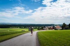 Сценарный взгляд девушки идя вниз с дороги в зеленой долине Стоковое фото RF