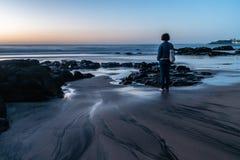 Сценарный взгляд женщины смотря на море против неба во время захода солнца стоковое изображение rf