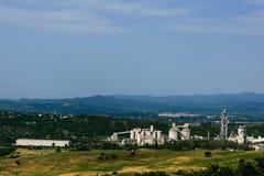 Сценарный взгляд ландшафта при огромная фабрика цемента окруженная зеленой вегетацией Стоковая Фотография