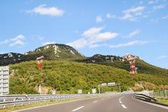 Сценарный взгляд на дороге шоссе водя до конца в Хорватии, Европе/электрических башнях, небе и облаках передачи в предпосылке Стоковое Изображение RF