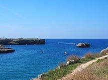 Сценарный взгляд Des Degeledor Calla в Ciutadellawith путь clifftop обозревая залива с голубым sunlit морем и быстроходным катеро стоковая фотография rf