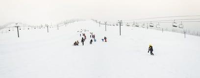 Сценарный взгляд малых людей вокруг лыжного курорта когда снежный день Стоковое Фото