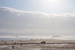 Сценарный взгляд на береге Lake Baikal в зиме и черном автомобиле едет вдоль скалистого побережья Стоковые Изображения
