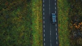 Сценарный воздушный конец-вверх взгляда сверху, трутень отслеживая черный автомобиль SUV двигая вдоль дороги шоссе вдоль пасмурно видеоматериал
