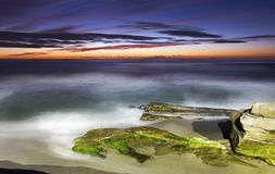 Сценарный заход солнца и драматические цвета неба на пляже La Jolla Калифорнии Windansea стоковое фото