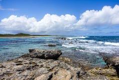 Сценарный карибский Seascape с голубым облачным небом и скалистым побережьем в переднем плане стоковая фотография