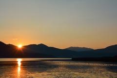 Сценарный ландшафт гребней и солнца горы излучает отражать в t стоковая фотография