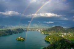 Сценарный панорамный вид на озеро кровоточил сверху с двойной радугой на небе Стоковые Изображения RF