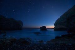 Сценарный скалистый seashore на заходе солнца под звездами Стоковое Фото