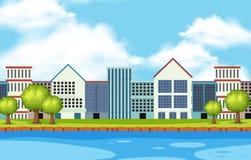 Сцена города с много зданий вдоль реки Стоковые Фотографии RF
