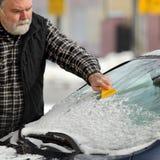 Сцена зимы, автомобиль og лобового стекла чистки водителя Стоковые Фотографии RF