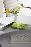 Сцена офиса с вазой цветка, пакетом подарка и клавиатурой на настольном компьютере Стоковое Изображение RF