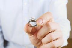 Сцена предложения захвата/замужества/свадьбы Закройте вверх человека вручая дорогое кольцо с бриллиантом платины золота к его нев Стоковые Фотографии RF